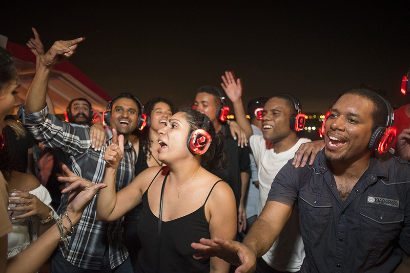 Group of people signing wearing glowing red headphones