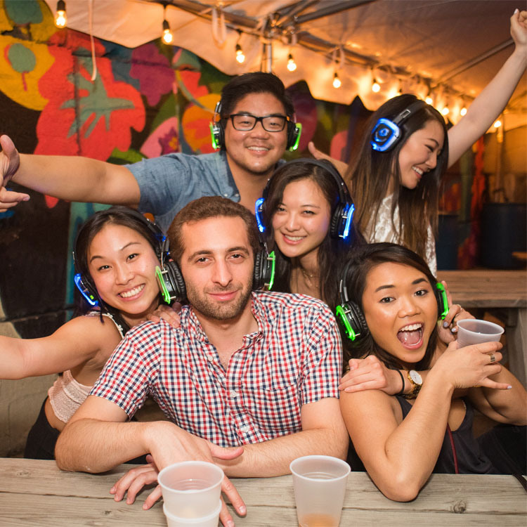 Group of people at a bar wearing silent disco headphones