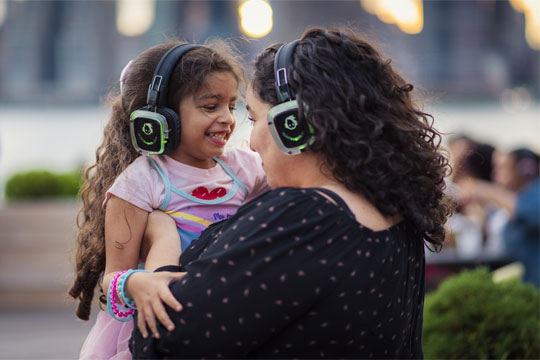 A mother holding her daughter wearing silent disco headphones